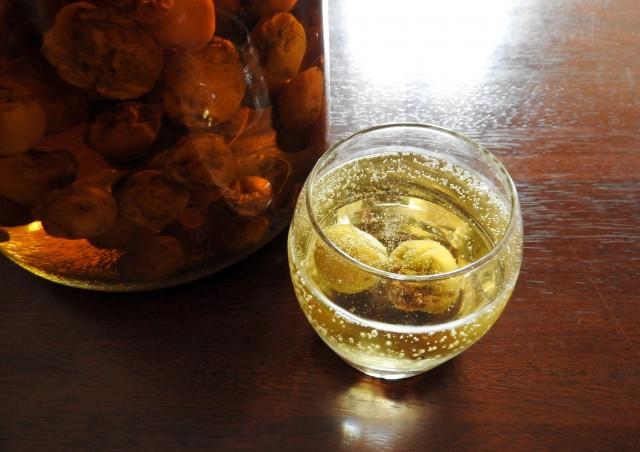 通販で銘酒を購入するなら三重県の酒屋【旨喜酒専門店 KOBA】へ-地酒や焼酎・梅酒や和リキュールも豊富に取り揃えております-木目のテーブルにソーダで割られた梅酒がグラスに注がれている画像